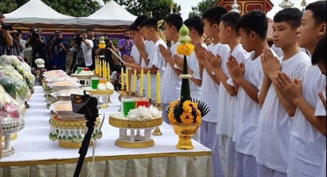 11 cầu thủ và huấn luyện viên Ekapol 25 tuổi mặc trang phục trắng, cùng nhau thắp lên những ngọn nến vàng, chắp tay cúi lạy trước tượng Phật trong buổi lễ trang trọng này. (Ảnh: Reuters)