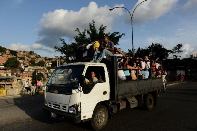 Người dân Venezuela đi trên một chiếc xe lồng trong khu ổ chuột Caracas. (Nguồn: AFP Photo/Federico PARRA)