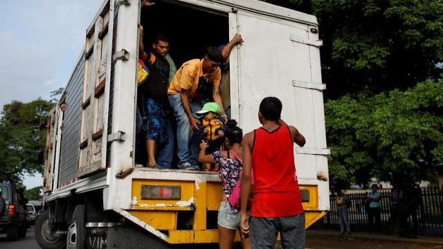 Một người đàn ông giúp một đứa trẻ lên một chiếc xe tải ở Valencia, Venezuela. (Nguồn: Reuters)