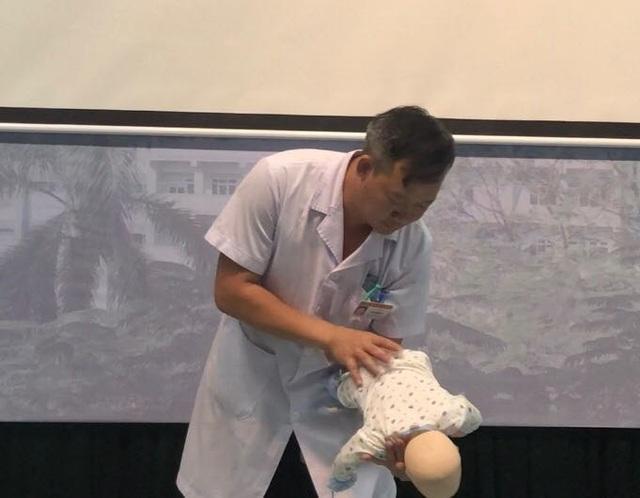Đặt trẻ nằm dọc cánh tay, bàn tay đỡ lấy cổ bé theo tư thế đầu dốc xuống để thực hiện vỗ lưng đẩy dị vật ra ngoài. Ảnh: H.Hải