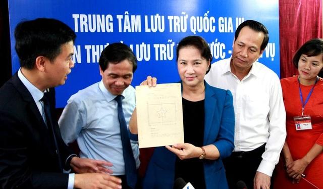 Chủ tịch Quốc Hội xem phiên bản tài liệu về một bản vẽ về lá Quốc kỳ.