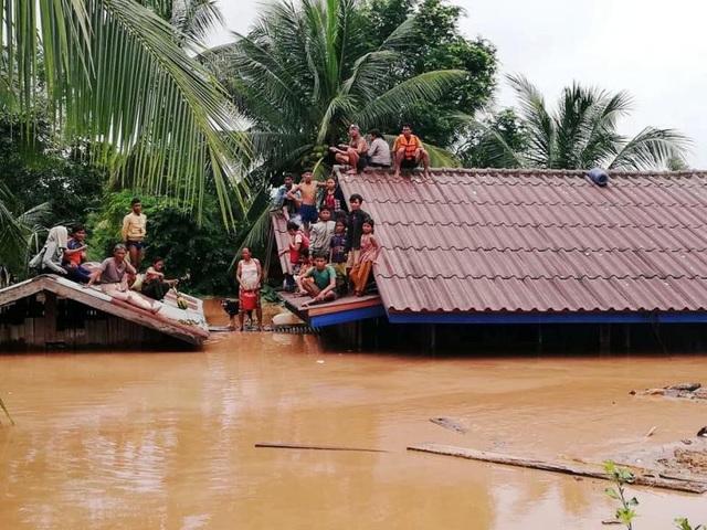 Nhiều người dân ở vùng hạ lưu ở tỉnh Attappeu, Lào phải leo lên mái nhà tránh lũ. (Ảnh: Getty)