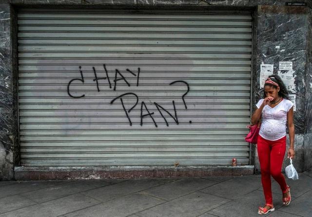 Một phụ nữ đi ngang qua một cửa hàng đóng kín cửa ở Caracas, Venezuela với dòng chữ Có bánh mì không? trên cửa. (Nguồn: Juan Barreto / AFP / Getty Images)