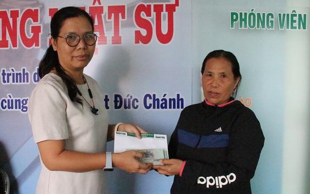 Nhà báo Toàn Thắng (bên trái) trao tiền bạn đọc giúp đỡ gia đình bà Bê