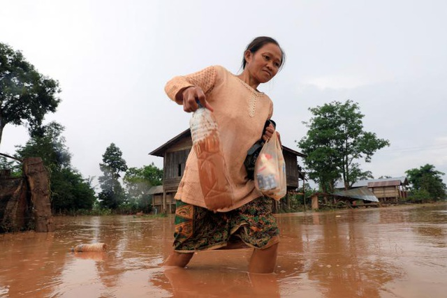 Một phụ nữ di chuyển khó khăn khi đường đi bị ngập nước bùn.
