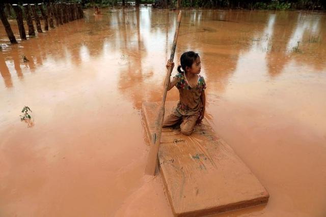 Bé gái sử dụng một tấm đệm làm phương tiện di chuyển qua khu vực ngập trong bùn đỏ.