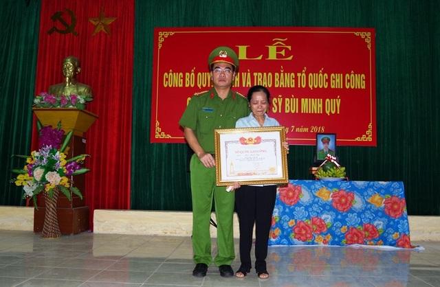 Thừa ủy quyền của Thủ tướng Chính phủ, Thượng tá Phạm Hữu Trường, Phó Giám đốc Công an tỉnh Gia Lai trao Bằng Tổ quốc ghi công cho mẹ Liệt sĩ Bùi Minh Quý.