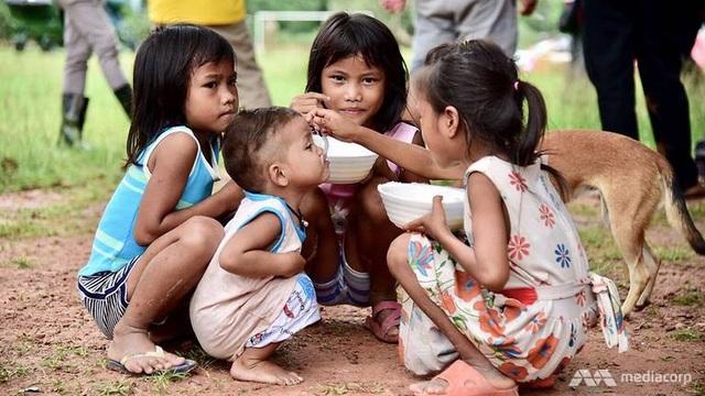 Những đứa trẻ ăn cháo tại trại sơ tán ở Sanamxai (Ảnh: Mediacorp)