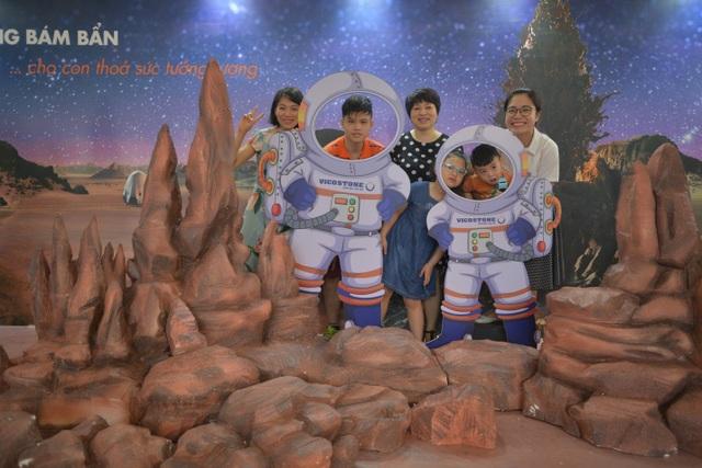 """Không gian sự kiện mô phỏng bề mặt của một hành tinh nhỏ với mô hình phi thuyền và nhiều phụ kiện của các phi hành gia, cho bé và cả gia đình lưu giữ lại khoảnh khắc cùng nhau """"khám phá vũ trụ""""."""
