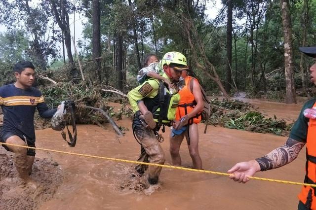 Đội cứu hộ Thái Lan cõng một em nhỏ qua sông tại tỉnh Attapeu (Ảnh: AFP)