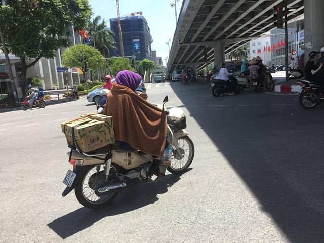 Trên phố Thái Hà (Hà Nội), một người phụ nữ phải sử dụng khăn choàng kín người làm dịu bớt cái nắng gay gắt như đổ lửa.