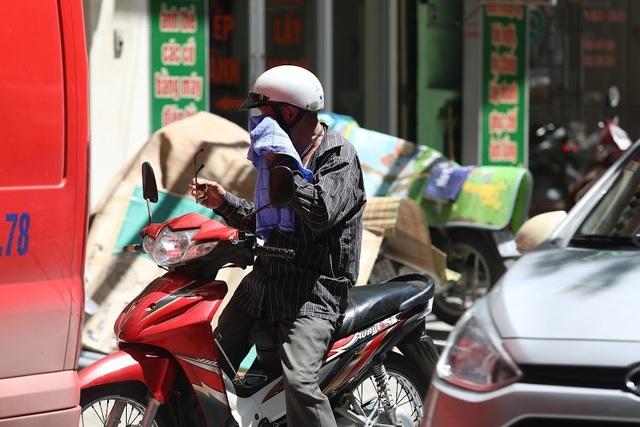 Vất vả nhất là những người lao động, khi phải oằn mình giữa trưa nắng để mưu sinh. Trong ảnh là một người đàn ông tranh thủ dùng khăn mặt ướt lau mồ hôi để giảm nhiệt khi đứng chờ đèn đỏ.