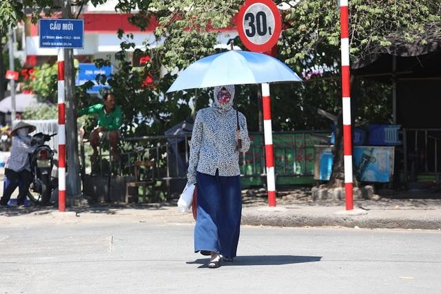 """Hơi nóng bốc lên trên vỉa hè khiến người đi đường có cảm giác bị ngộp thở, khó chịu. Nhiều chị em """"chế"""" ra đủ mọi cách để chống nắng."""