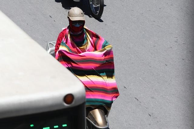 Một người phụ nữ phải chùm một chiếc chăn mỏng để che nắng khi di chuyển ngoài đường