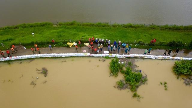 Khi mực nước áp sát mặt đê, người dân trong vùng cùng lực lượng quân đội phải gắp bao tải cát để chống nước tràn qua đê.