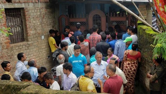 Hàng xóm tụ tập bên ngoài căn hộ của các nạn nhân. (Ảnh: PTI)