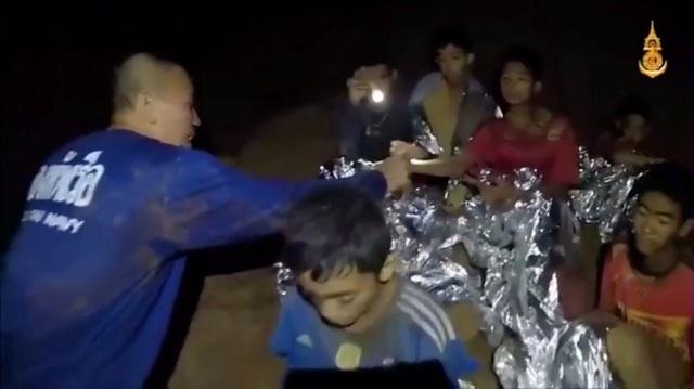 Hai thành viên của đội cứu hộ soi đèn để chăm sóc cho các cậu bé (Ảnh: Reuters)