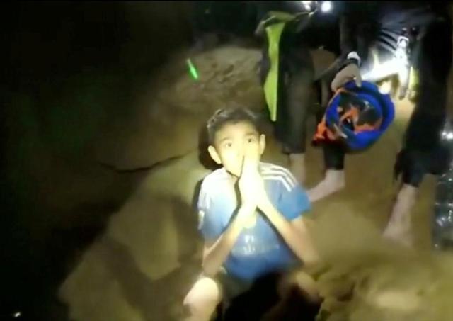 Một cậu bé chắp tay gửi lời cảm ơn tới đội cứu hộ (Ảnh: Reuters)