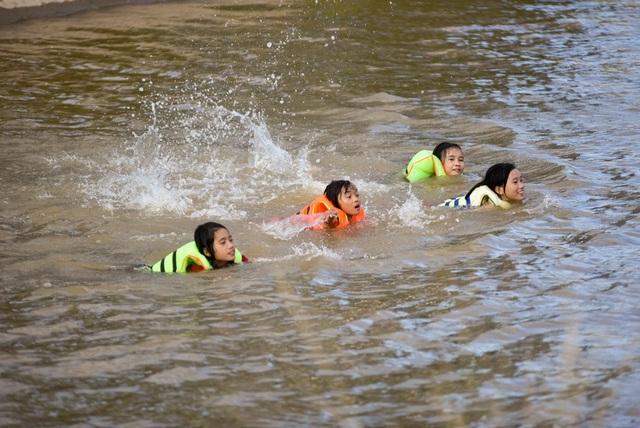 Các em nhỏ thỏa sức tắm trên dòng nước mát lạnh.