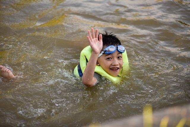 Một em nhỏ đang vui vẻ tắm trên dòng nước mát lạnh.