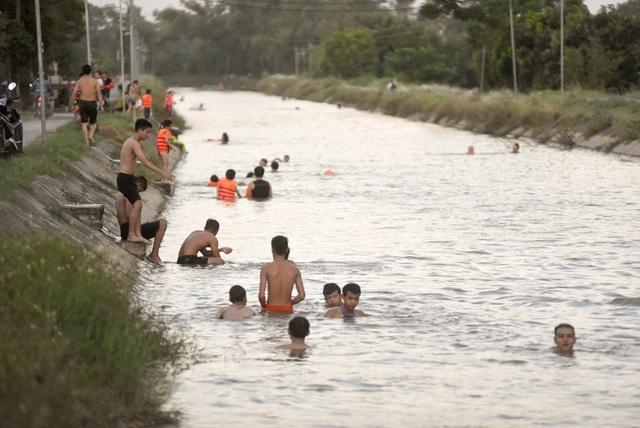 """Hà Nội: Mương nước thành """"bể bơi"""" giải nhiệt ngày nắng nóng - 14"""