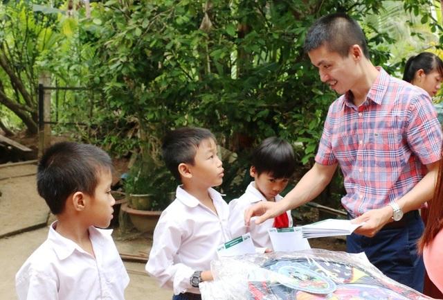 Nhà báo Phạm Tuấn Anh - Phó Tổng biên tập báo Dân trí trao các suất học bổng cho các em HS có hoàn cảnh đặc biệt khó khăn ở địa phương