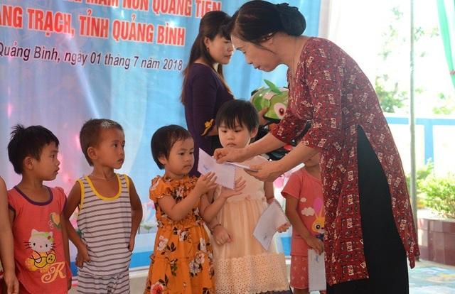 Bà Phạm Thị Bích Lựa, Chủ tịch Hội Khuyến học tỉnh Quảng Bình trao học bổng của Báo Dân trí cho các em học sinh Trường Mầm non Quảng Tiến trong dịp khánh thành phòng học Dân trí tại ngôi trường này