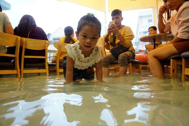 Trẻ em thích thú vui đùa với những chú cá trong hồ nước.