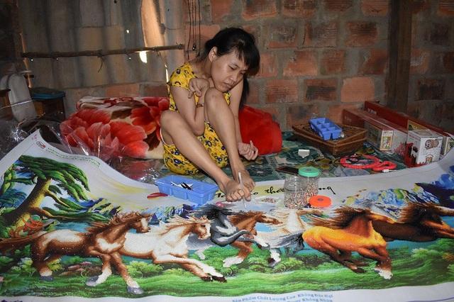 Nguyễn Thị Lệ Hằng dùng chân, tỉ mỉ đính những viên đá nhỏ lên bức tranh