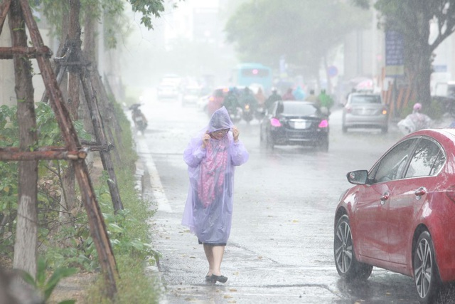 Người phụ nữ đi bộ dưới mưa để cảm nhận được sự mát mẻ chút ít, sau gần 10 ngày nắng nóng kinh hoàng.