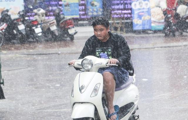 Cơn mưa trút xuống khiến người đi đường cảm thấy thỏa mãn, thích thú bởi trước đó họ phải đối mặt với cái nóng bỏng rát trong nhiều ngày.