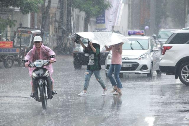 Cơn mưa bất chợt đổ xuống khiến người đi đường trở tay không kịp.