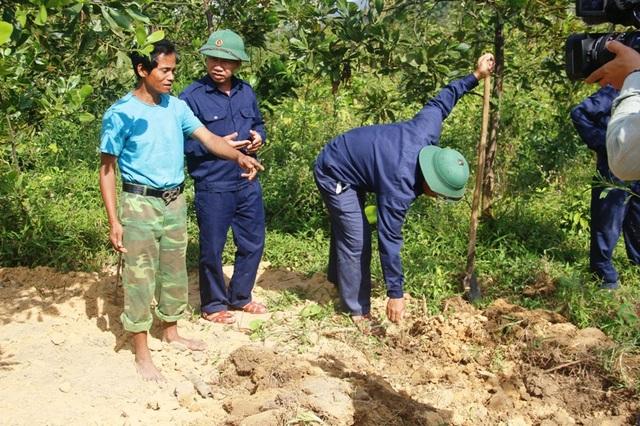 Thiếu tá Trần Mạnh Hà và già Hồ Văn Oi trao đổi thông tin về khu vực tìm kiếm hài cốt liệt sĩ