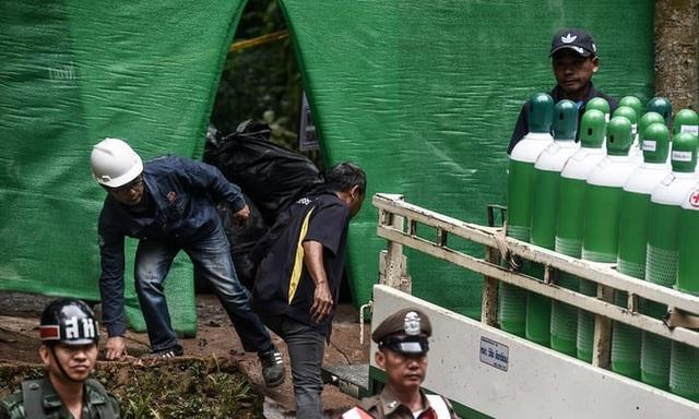 Giới chức Thái Lan cho biết mực nước trong hang Tham Luang đã giảm đáng kể từ ngày 7/7 và đội cứu hộ đã sẵn sàng để đưa 13 người mắc kẹt ra khỏi hang. Trong ảnh: Các thành viên đội cứu hộ tập kết bình oxy tại hang Tham Luang trước khi bắt đầu chiến dịch giải cứu. (Ảnh: AFP)