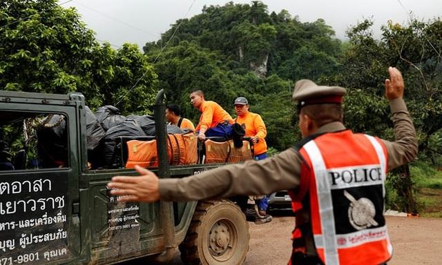 Nếu mọi điều kiện thuận lợi, những người đầu tiên dự kiến được đưa ra khỏi hang sớm nhất vào 21 giờ hôm nay. Trong ảnh: Cảnh sát Thái Lan chỉ đường cho xe chở lực lượng cứu hộ. (Ảnh: Reuters)