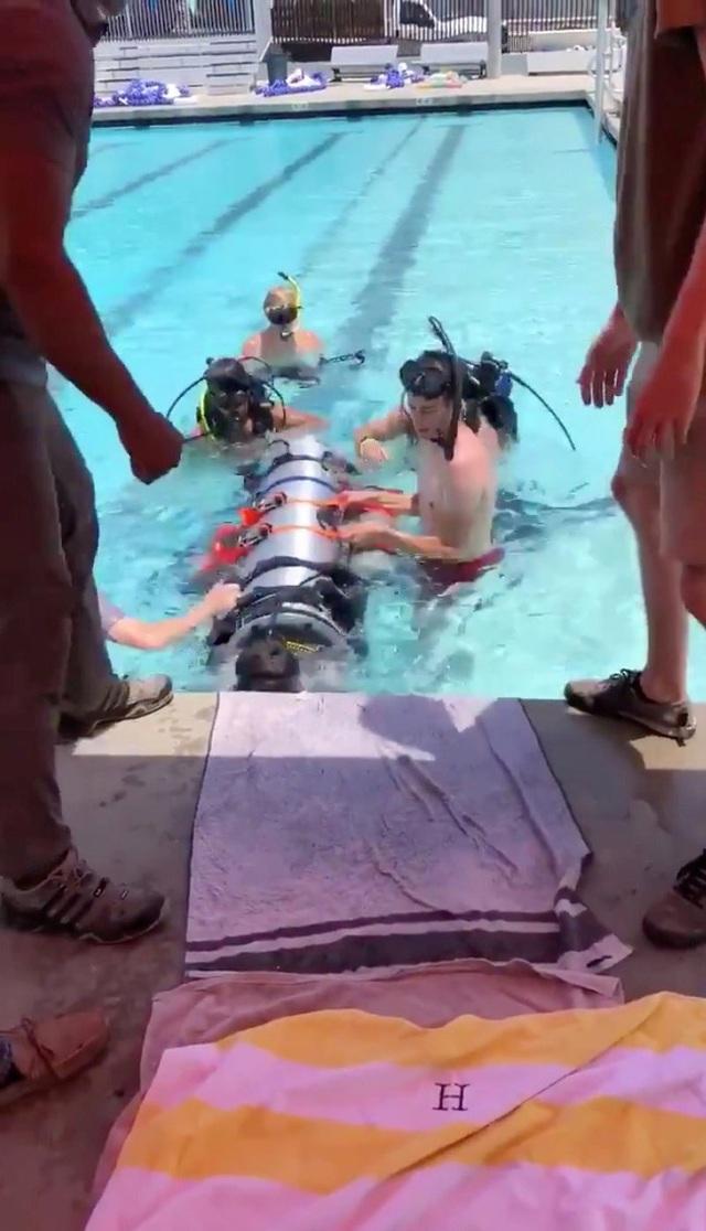 Elon Musk đăng video thử nghiệm tàu ngầm mini tại bể bơi và dựng các rào cản mô phỏng các khe hẹp trong hang. Thậm chí, một đứa trẻ cũng được đưa vào bên trong tàu ngầm để thử nghiệm. (Ảnh: Reuters)
