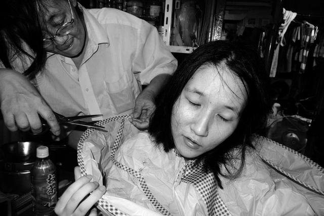 Mẹ cắt tóc cho con gái.