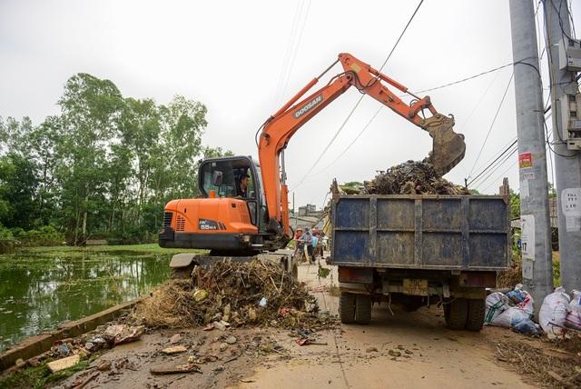 Sau ngập, nhiều rác ứ đọng khắp nơi, các phương tiện cơ giới được huy động để dọn dẹp.
