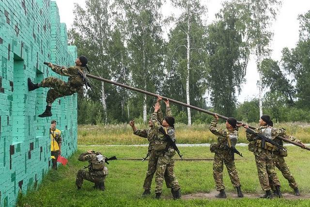 Các binh sĩ thuộc Lực lượng Vũ trang Cộng hòa Kazakhstan phối hợp cùng nhau để vượt qua bức tường. (Ảnh: TASS)