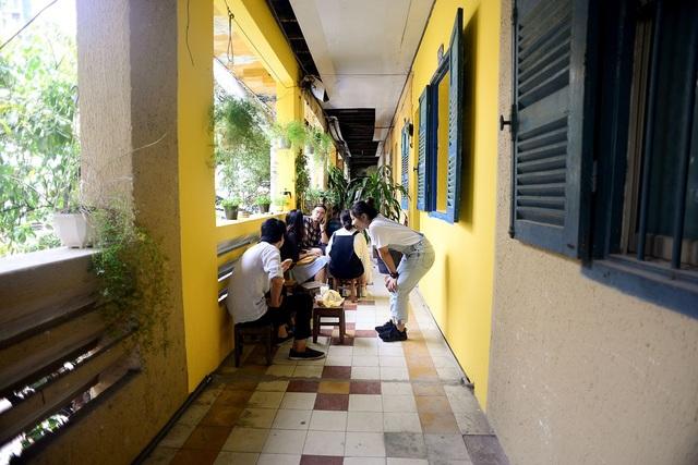 Dọc hành lang được đặt thêm những chiếc ghế gỗ cho khách ngồi uống cà phê ngắm phố phường.