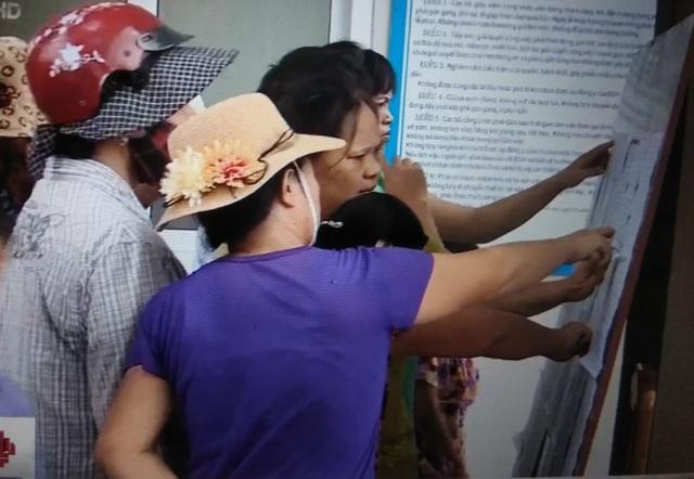 Phụ huynh đang trực tiếp xem thông tin tuyển sinh được dán ở cổng Trường tiểu học Cao Báo Quát.