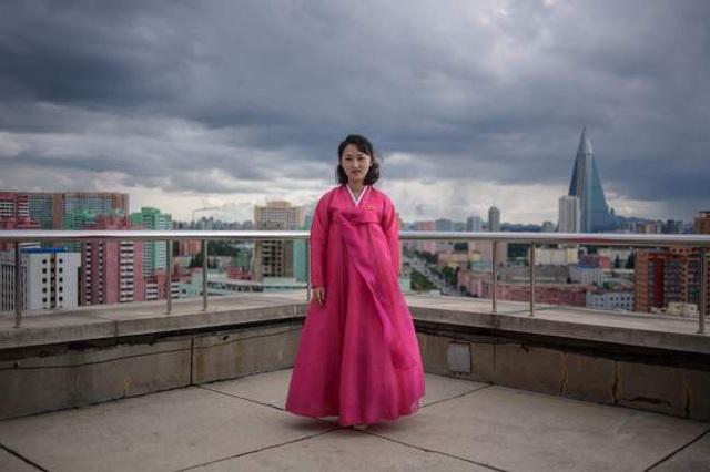 Bức ảnh chụp hướng dẫn viên du lịch Ju Hye-yon ngày 16/6 trên khu vực ngắm cảnh tại Khải Hoàn Môn ở Bình Nhưỡng. Đây là công trình được xây dựng nhằm tưởng nhớ về cuộc chiến chống lại Đế quốc Nhật năm 1925-1945 của dân tộc Triều Tiên. Công trình này được lấy ý tưởng từ Khải Hoàn Môn ở Paris, Pháp. Tại thành phố Bình Nhưỡng vốn chuộng những tông màu nhạt và trầm, chiếc hanbok (trang phục truyền thống của Triều Tiên) màu hồng rực rỡ của cô Ju khiến cô trở nên nổi bật.