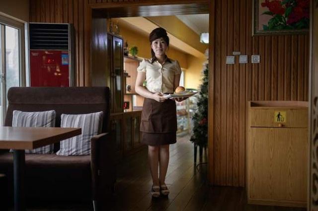 Bồi bàn Rim Ok-hyang, 20 tuổi, chụp ảnh tại một cửa hàng bánh mì kẹp hamburger ở Bình Nhưỡng vào ngày 18/7.