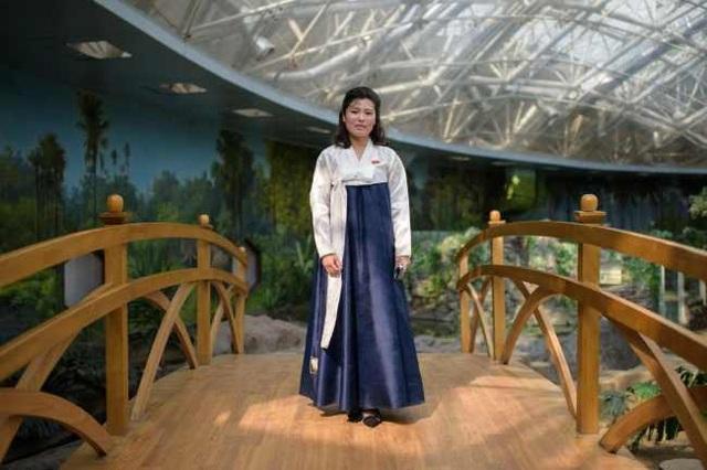 Hướng dẫn viên Kim Song-hui, 26 tuổi, chụp ảnh ngày 29/7 tại sở thú trung tâm ở Bình Nhưỡng. Cô Kim mặc một bộ hanbok trắng xanh đầy duyên dáng.