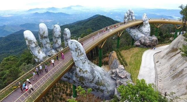Chuyên trang du lịch - khám phá National Geographic nhấn trọng tâm vào chi tiết hai bàn tay khổng lồ nâng đỡ cây cầu.