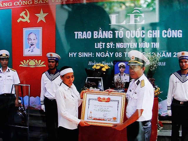 Chị Cao Thị Thúy nhận bằng Tổ quốc ghi công chồng mình, liệt sĩ Nguyễn Hữu Thi . Ảnh: CTV