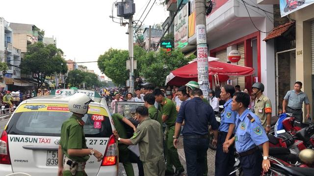 Lực lượng chức năng áp giải nghi phạm về trụ sở công an để điều tra