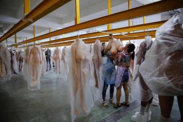 Công nhân treo búp bê tình dục trong nhà kho tại nhà máy WMDOLL ở Trung Sơn, tỉnh Quảng Đông