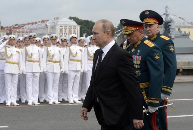 Tổng thống Nga Vladimir Putin cùng Bộ trưởng Quốc phòng Sergei Shoigu (giữa) và cựu Tư lệnh Quân khu phía Tây Andrey Kartapolov tham gia lễ duyệt binh kỷ niệm Ngày Hải quân ở St. Petersburg. Ông Kartapolov nay được bổ nhiệm làm Chủ nhiệm Tổng cục Chính trị quân đội Liên bang Nga (Ảnh: AFP)