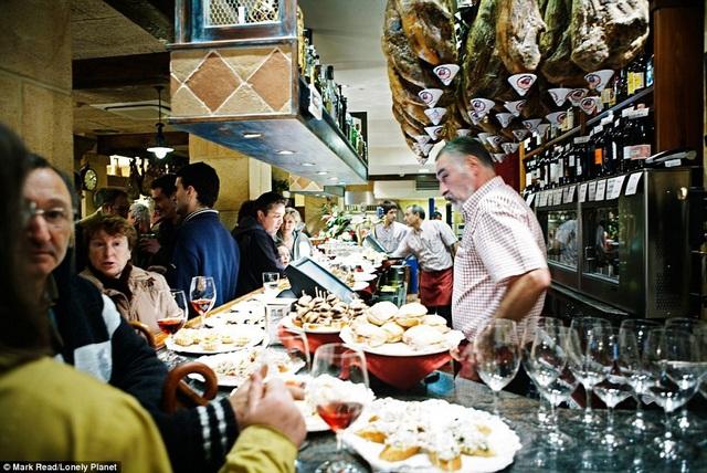 """Đứng ở vị trí đầu bảng là """"pintxos"""" ở San Sebastian (Tây Ban Nha). Món này gồm có bánh mì thái lát ăn kèm với những loại nhân đa dạng. Đây là món ăn nhẹ, thường phục vụ trong quán bar, quán rượu, cũng là món thường dùng khi người Tây Ban Nha ngồi với bạn bè, người thân. """"Pintxos"""" mang nhiều ý nghĩa trong sinh hoạt cộng đồng đối với người Tây Ban Nha."""